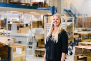 Bilden visar Emelie Blomqvist, en av våra medarbetare på ÅJ Distribution, i vår produktionshall för logistik av marknadsmaterial för säljorganisationer och kedjeföretag inom Retail.